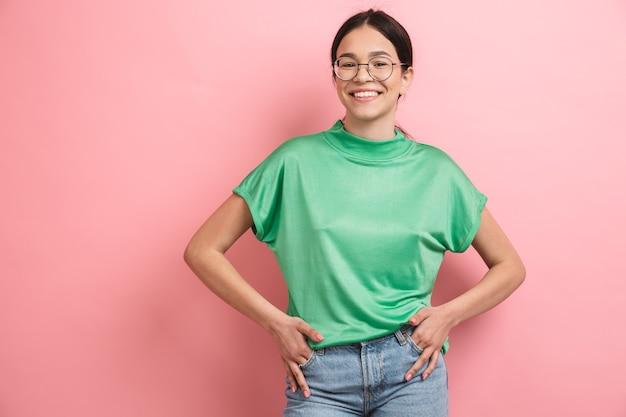 Młoda kaukaska dziewczyna w okrągłych okularach uśmiechnięta i radująca się z przodu, odizolowana na różowej ścianie