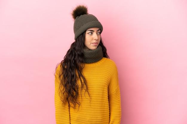 Młoda kaukaska dziewczyna w zimowym kapeluszu na fioletowym tle, patrząc w bok