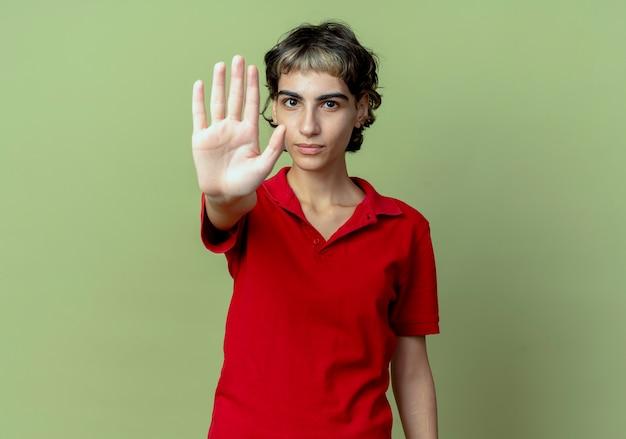Młoda kaukaska dziewczyna z fryzurą pixie gestykuluje stop i patrzy na kamerę odizolowaną na oliwkowozielonym tle z miejsca na kopię