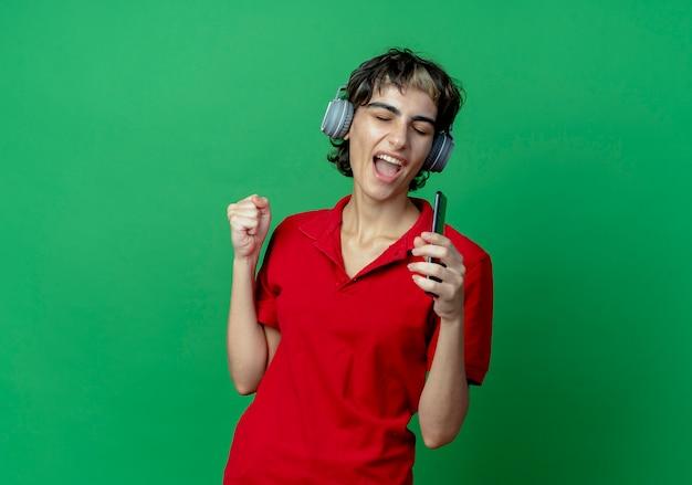 Młoda kaukaska dziewczyna z fryzurą pixie w słuchawkach słucha muzyki trzymając telefon komórkowy udaje, że śpiewa, używając telefonu jako mikrofonu z zaciśniętą pięścią i zamkniętymi oczami