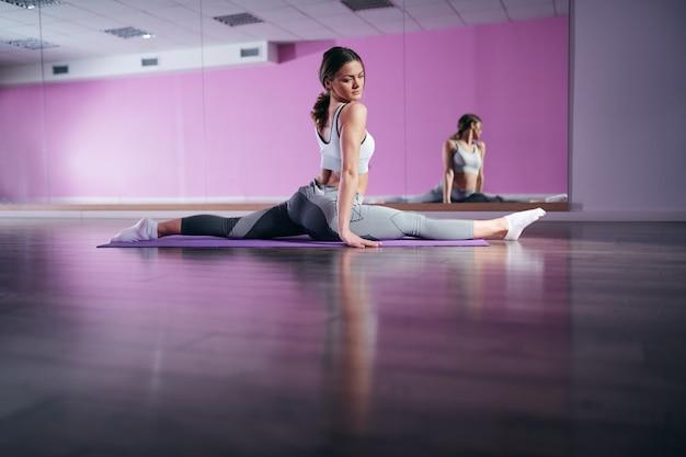 Młoda kaukaska elastyczna brunetka w odzieży sportowej robi ćwiczenia na macie z rozłożonymi nogami. w lustrze w tle.