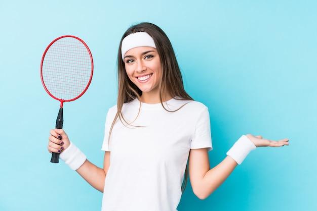 Młoda kaukaska kobieta bawić się badminton odizolowywającego pokazywać copyspace na dłoni i trzymać inną rękę na talii.