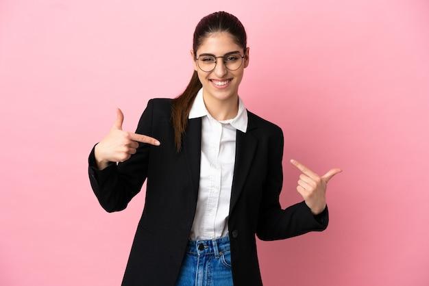Młoda kaukaska kobieta biznesu odizolowana na różowym tle dumna i zadowolona z siebie