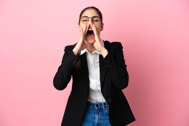 Młoda kaukaska kobieta biznesu odizolowana na różowym tle krzyczy i ogłasza coś