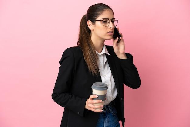 Młoda kaukaska kobieta biznesu odizolowana na różowym tle trzymająca kawę na wynos i telefon komórkowy