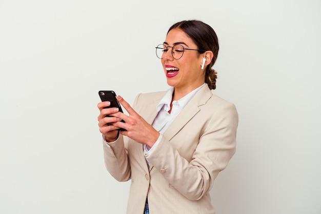Młoda kaukaska kobieta biznesu wpisuje wiadomość za pomocą telefonu komórkowego