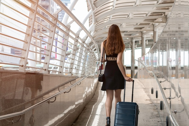 Młoda kaukaska kobieta chodzi z walizką w nowożytnym lotniskowym terminal. tylny widok szczęśliwy podróżnik.