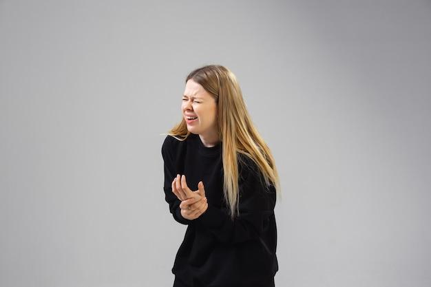 Młoda kaukaska kobieta cierpi na ból nadgarstka