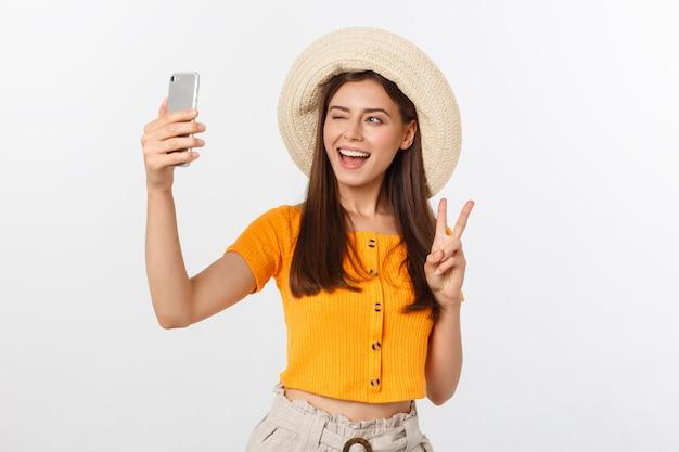 Młoda kaukaska kobieta cieszy się selfie z ona odizolowywającą na białym lato podróży pojęciu.