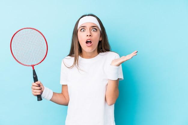 Młoda kaukaska kobieta gra w badmintona na białym tle zaskoczony i zszokowany.