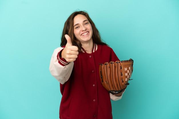 Młoda kaukaska kobieta gra w baseball na białym tle na niebieskim tle z kciukami do góry, ponieważ stało się coś dobrego