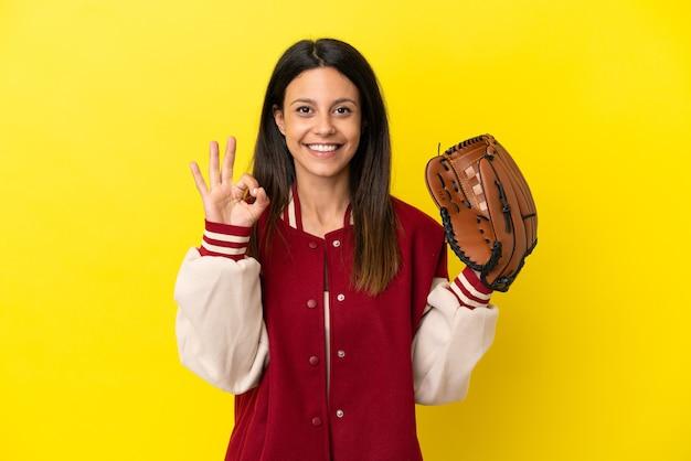 Młoda kaukaska kobieta gra w baseball na białym tle na żółtym tle pokazując znak ok palcami