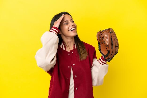 Młoda kaukaska kobieta gra w baseball na żółtym tle i dużo się uśmiecha