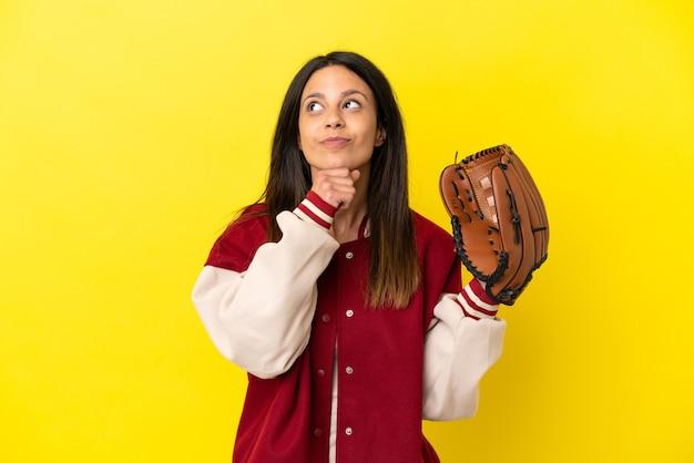 Młoda kaukaska kobieta gra w baseball na żółtym tle i patrzy w górę