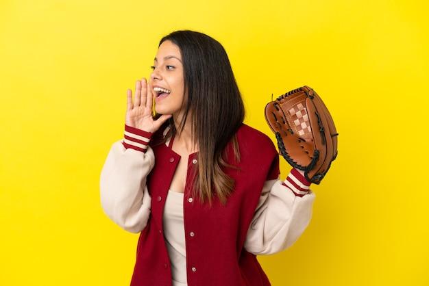 Młoda kaukaska kobieta gra w baseball na żółtym tle krzycząc z szeroko otwartymi ustami