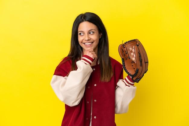 Młoda kaukaska kobieta gra w baseball na żółtym tle, patrząc w bok i uśmiechając się