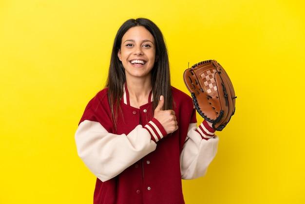Młoda kaukaska kobieta gra w baseball na żółtym tle, pokazując gest kciuka w górę