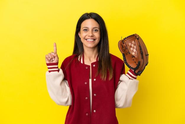 Młoda kaukaska kobieta gra w baseball na żółtym tle pokazując i podnosząc palec na znak najlepszych