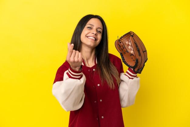 Młoda kaukaska kobieta gra w baseball na żółtym tle robiąc gest pieniędzy