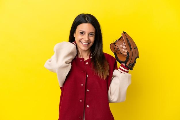 Młoda kaukaska kobieta gra w baseball na żółtym tle śmiejąc się