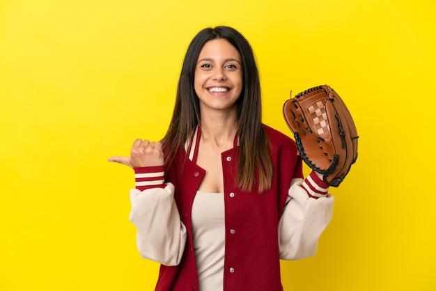 Młoda kaukaska kobieta gra w baseball na żółtym tle, wskazując na bok, aby zaprezentować produkt