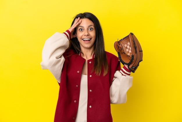 Młoda kaukaska kobieta gra w baseball na żółtym tle z wyrazem zaskoczenia