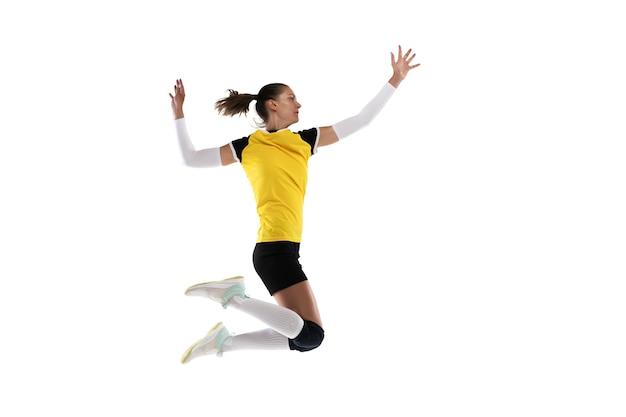 Młoda kaukaska kobieta gra w siatkówkę na białej ścianie studia