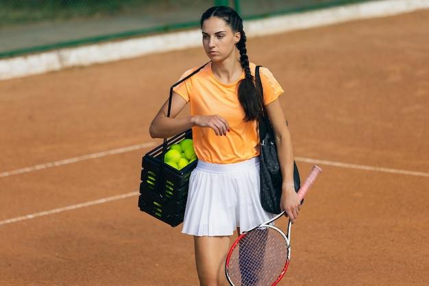 Młoda kaukaska kobieta gra w tenisa na korcie tenisowym na zewnątrz