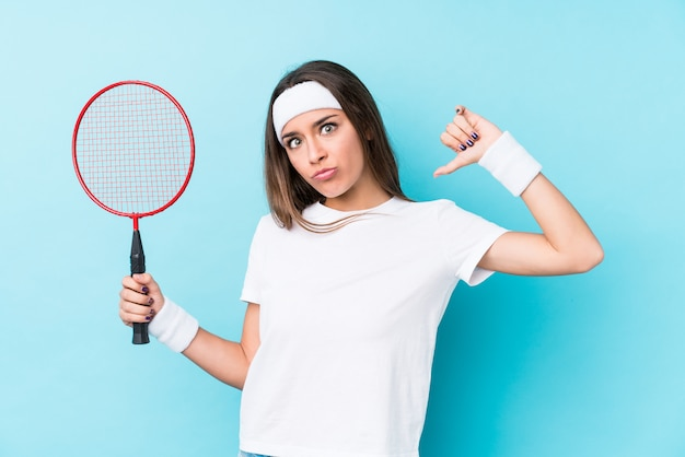 Młoda kaukaska kobieta grająca w badmintona na białym tle czuje się dumna i pewna siebie.