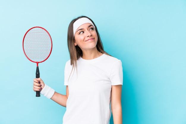Młoda kaukaska kobieta grająca w badmintona na białym tle marzy o osiągnięciu celów i zamierzeń