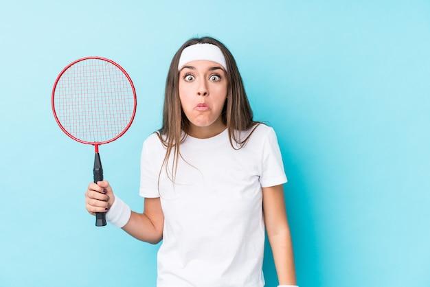 Młoda kaukaska kobieta grająca w badmintona wzrusza ramionami i wprawia w osłupienie otwarte oczy.