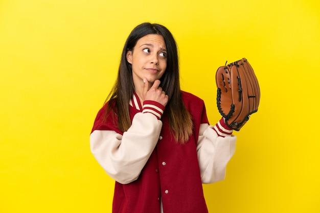 Młoda kaukaska kobieta grająca w baseball na żółtym tle mająca wątpliwości