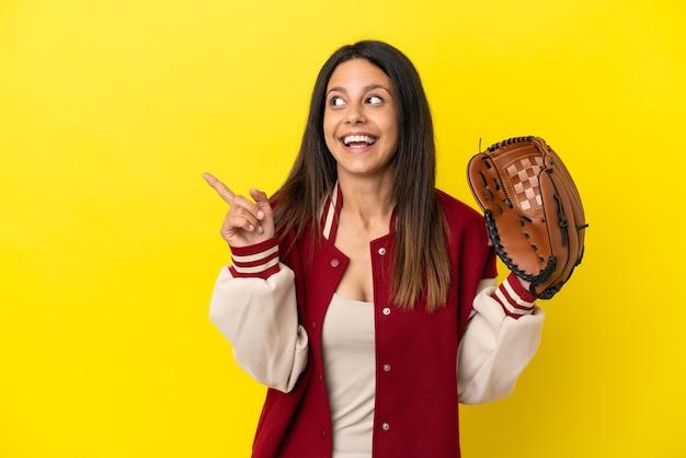 Młoda kaukaska kobieta grająca w baseball na żółtym tle, zamierzająca zrealizować rozwiązanie, podnosząc palec w górę