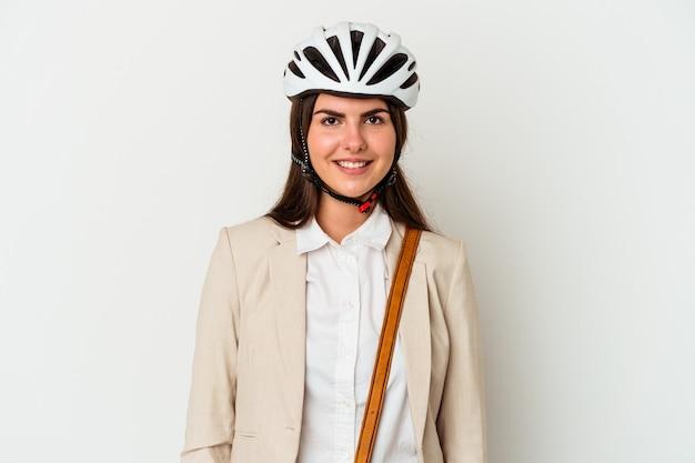 Młoda kaukaska kobieta jedzie na rowerze do pracy na białym tle szczęśliwa, uśmiechnięta i wesoła.