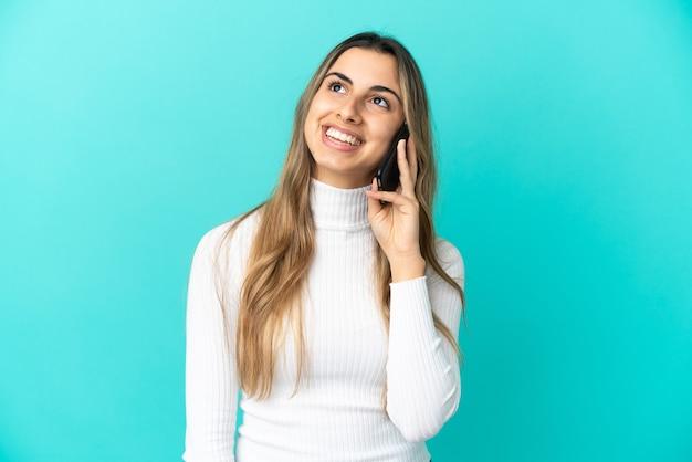 Młoda kaukaska kobieta korzystająca z telefonu komórkowego na białym tle, myśląca o pomyśle, patrząc w górę