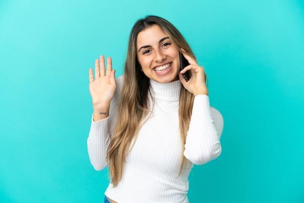 Młoda kaukaska kobieta korzystająca z telefonu komórkowego na białym tle na niebieskim tle, pozdrawiając ręką ze szczęśliwym wyrazem twarzy