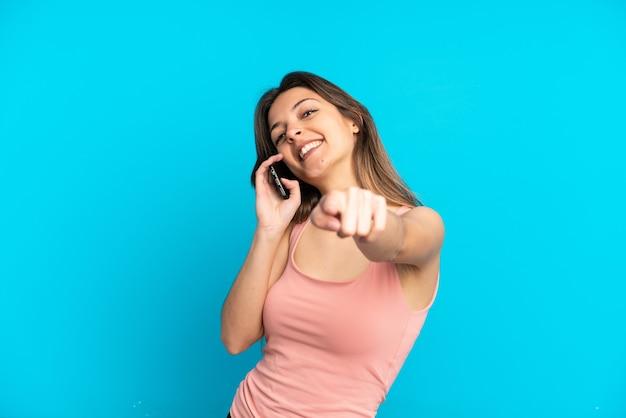 Młoda kaukaska kobieta korzystająca z telefonu komórkowego na białym tle na niebieskim tle, wskazując przód z radosnym wyrazem twarzy