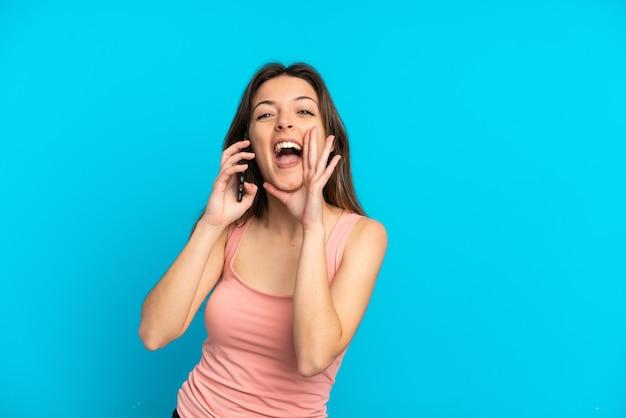 Młoda kaukaska kobieta korzystająca z telefonu komórkowego odizolowanego na niebieskiej ścianie krzyczy z szeroko otwartymi ustami