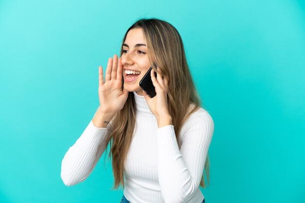Młoda kaukaska kobieta korzystająca z telefonu komórkowego odizolowanego na niebieskim tle krzyczy z szeroko otwartymi ustami