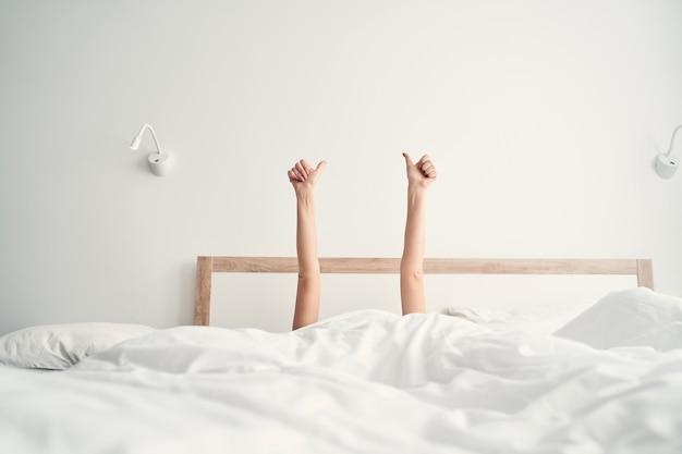 Młoda kaukaska kobieta leżąca bezsennie w swoim łóżku z rękami uniesionymi w powietrzu