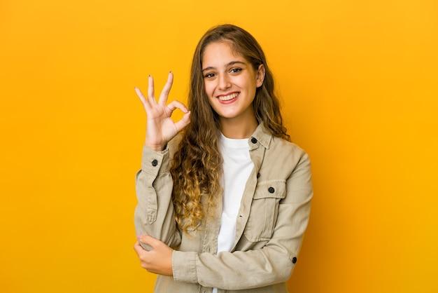 Młoda kaukaska kobieta mruga okiem i trzyma ręką dobry gest.
