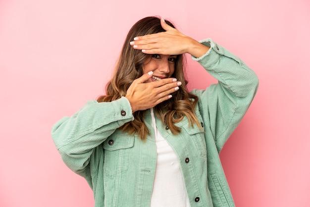 Młoda kaukaska kobieta mruga z przodu przez palce, zawstydzona zakrywająca twarz