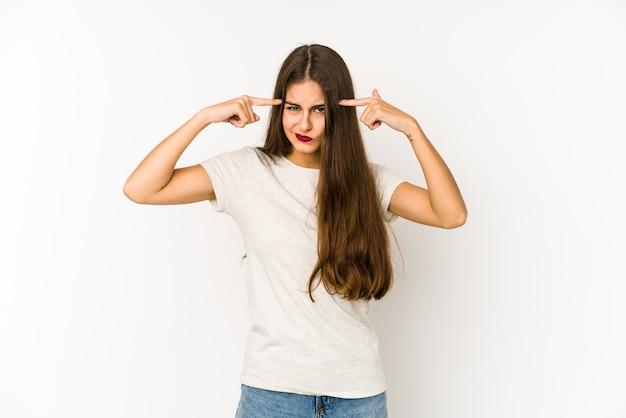 Młoda kaukaska kobieta na białej ścianie skupiona na zadaniu, trzymając wskazującą głowę palcami wskazującymi.