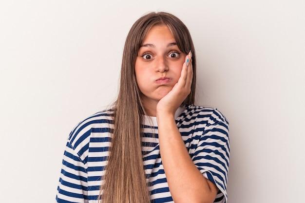 Młoda kaukaska kobieta na białym tle dmucha w policzki, ma zmęczony wyraz twarzy. koncepcja wyraz twarzy.