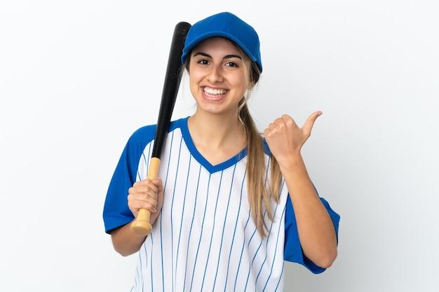 Młoda kaukaska kobieta na białym tle gra w baseball i wskazuje na bok, aby zaprezentować produkt