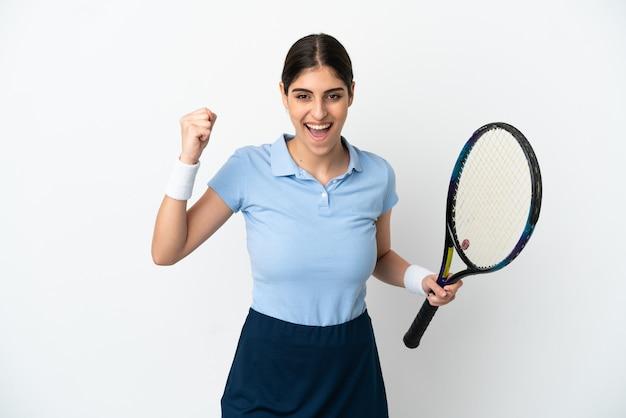 Młoda kaukaska kobieta na białym tle gra w tenisa i świętuje zwycięstwo