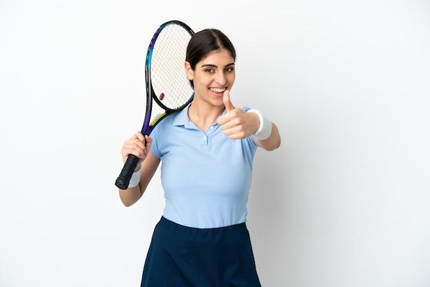 Młoda kaukaska kobieta na białym tle gra w tenisa i z kciukiem do góry