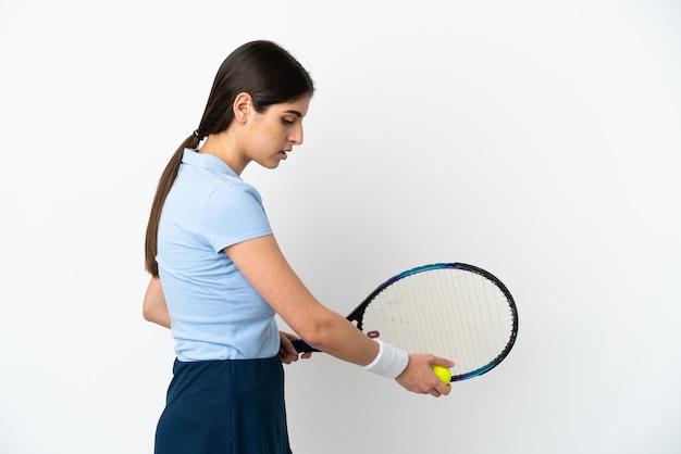 Młoda kaukaska kobieta na białym tle gra w tenisa