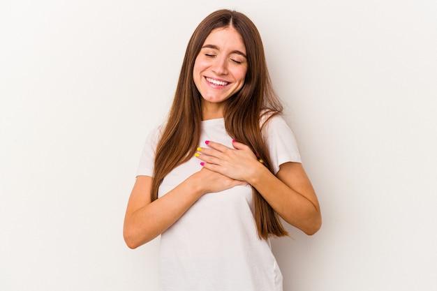 Młoda kaukaska kobieta na białym tle ma przyjazny wyraz, przyciskając dłoń do klatki piersiowej. koncepcja miłości.