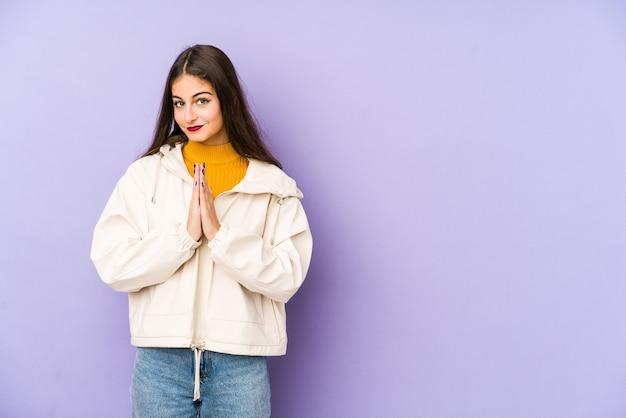 Młoda kaukaska kobieta na białym tle na fioletowym modląc się, okazując oddanie, osoba religijna szuka boskiej inspiracji.
